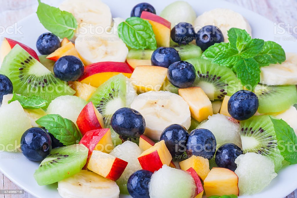 fresh fruit salad with kiwi, berries, banana and fresh mint