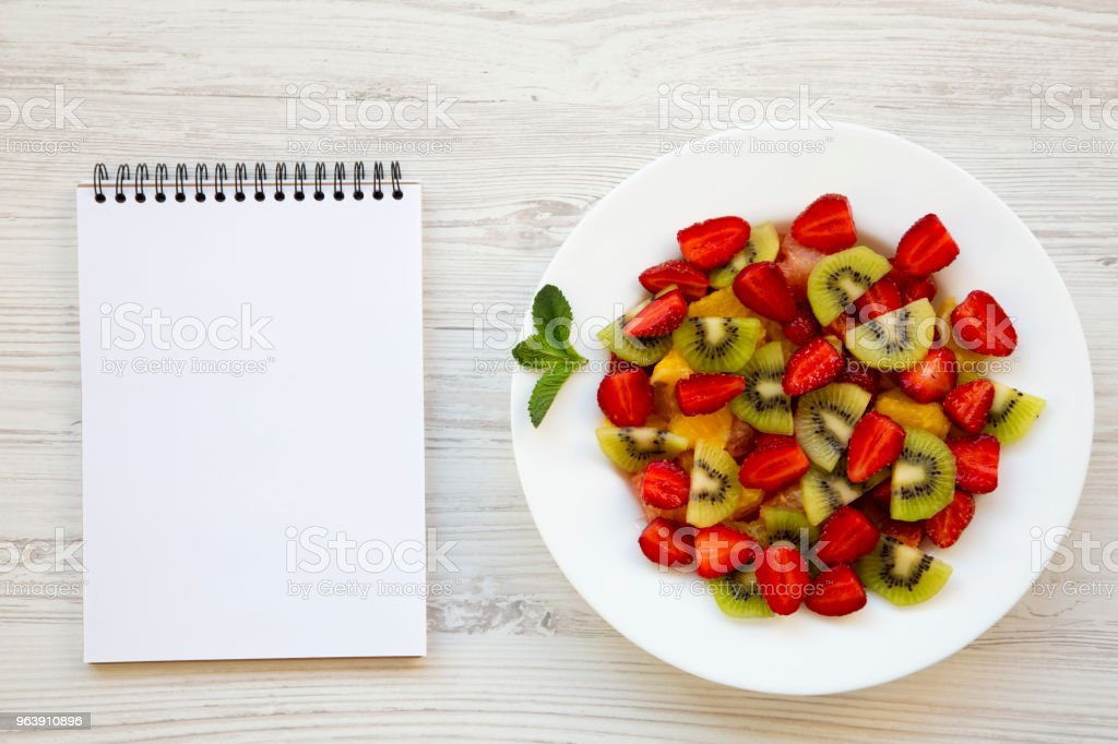 Fresh fruit salad with notepad on white wooden background, top view. - Royalty-free Blank Stock Photo