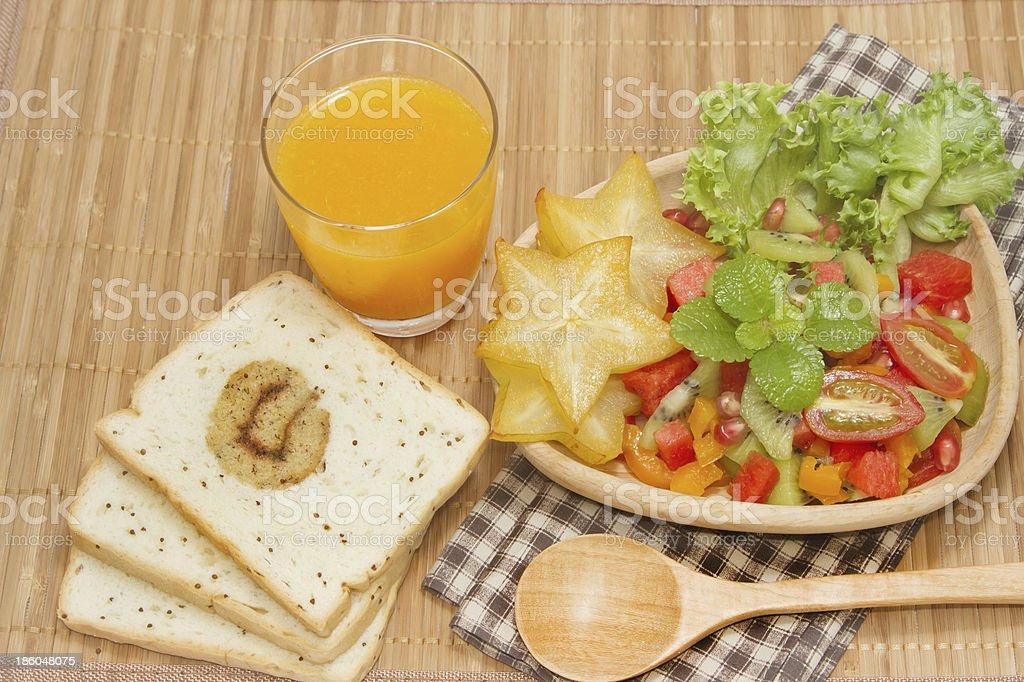 Fresh fruit salad with orange juice and slice bread, royalty-free stock photo
