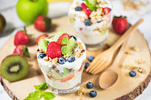 Fresh fruit salad with yogurt and berry in glass on wooden plate background. Healthy Eating. Selective focus.