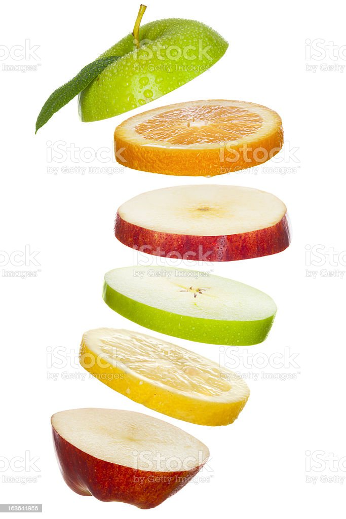 Fresh Fruit Slices; Apples, Lemon, Orange Tossed in Air stock photo