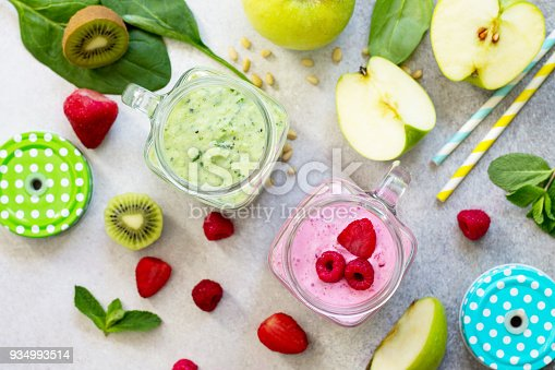 istock Fresh fruit smoothie and green smoothies on a gray stone or slate background. Healthy vegan food concept. 934993514