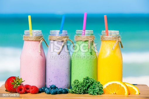 Assortment of fruit smoothies against a beach background.