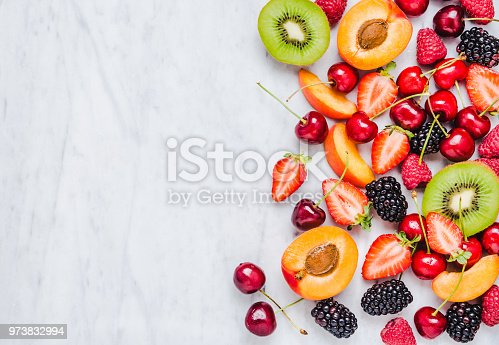Fresh fruits and berries frame copy space on marble background directly above .