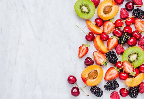 istock Fresh fruits and berries on marble background. 973832994