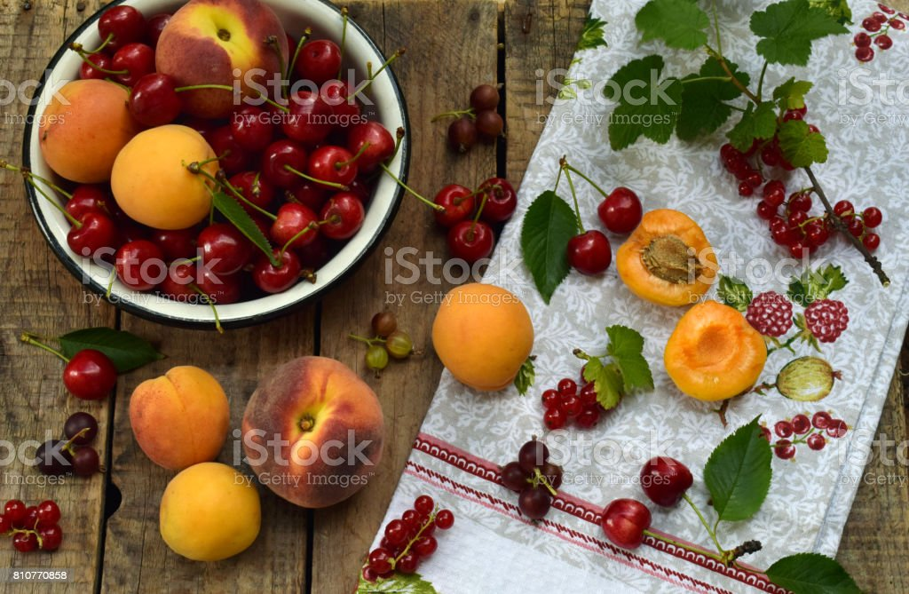 Fresh fruits and berries on wooden background. Ripe sweet cherry, currants, peach and apricot in bowl on the kitchen table. stock photo