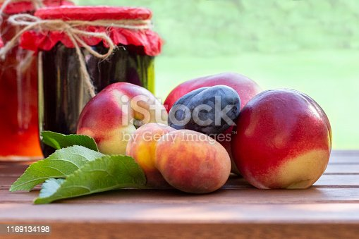 Fresh fruits and homemade jars of jam on wooden table in blurred natural  garden background. Preserves of peaches, nectarines, plums