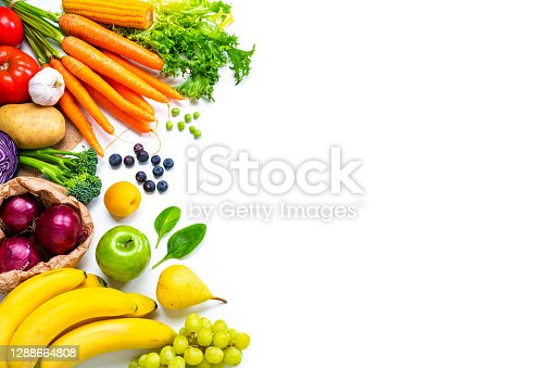 Food backgrounds: overhead view of healthy fresh organic multicolored fruits and vegetables arranged at the left border of a white background making a frame and leaving useful copy space for text and/or logo at the right. The composition includes carrots, tomato, corn, spinach, green peas, Spanish onion, lettuce, broccoli, radish, cabbage, potato, garlic, banana, green apple, pear, grape, blueberries and peach. High resolution 42Mp outdoors digital capture taken with SONY A7rII and Zeiss Batis 25mm F2.0 lens