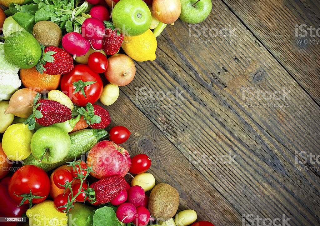 Fresh fruits and vegetables on the old wooden board royalty-free stock photo