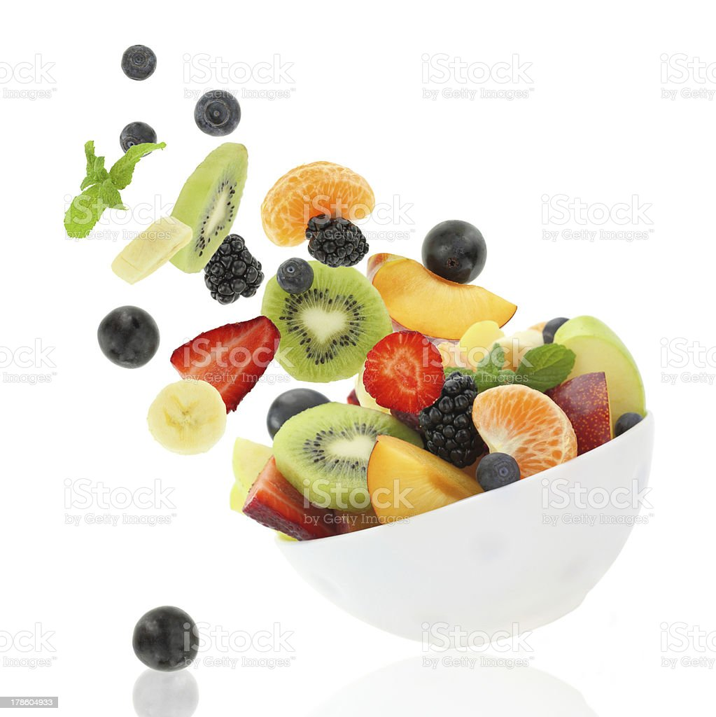 Fresh fruits coming out from a bowl stock photo