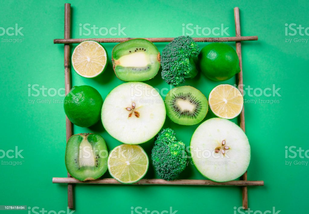 Fresh fruits in a square frame on a green table. Healthy eating stock photo