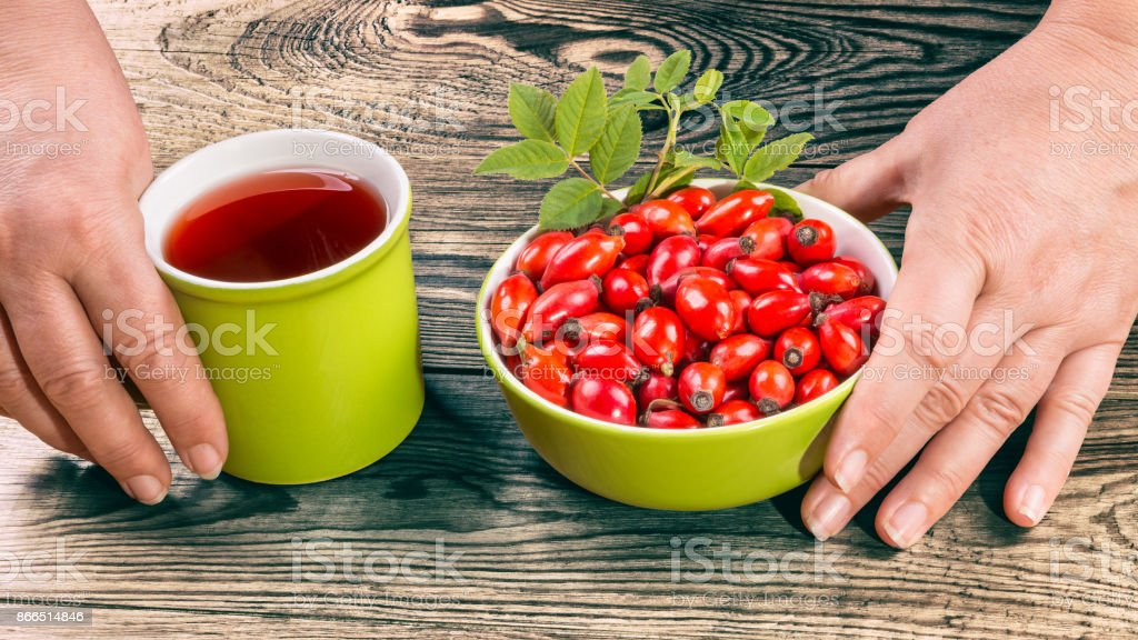 Fresh fruits of wild rose and hip tea on brown wooden background stock photo