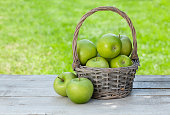 Fresh garden green apples in basket. On outdoor table with copy space for your text