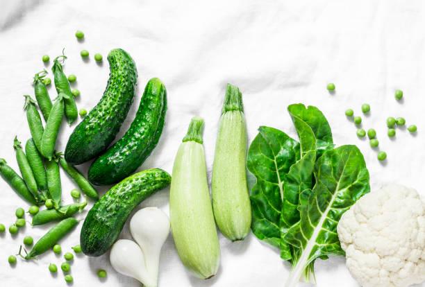 frische bio grüne gartengemüse - gurken, zucchini, mangold, erbsen, zwiebeln, blumenkohl auf einem hellen hintergrund, ansicht von oben. flache lay, textfreiraum - mangoldgemüse stock-fotos und bilder