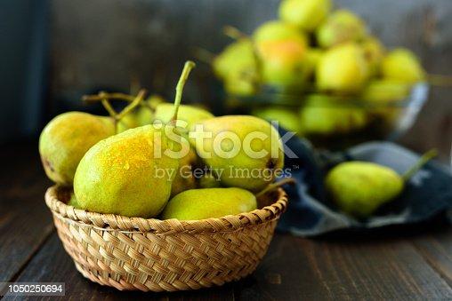 istock Fresh garden pears on dark wooden table 1050250694