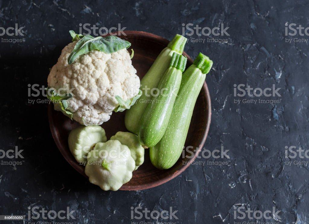 Fresh garden vegetables - cauliflower, zucchini, squash on a dark background, top view. Cooking ingredients stock photo