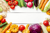 Fresh garden vegetarian food. Autumn seasonal image of farmer table with mushrooms, rye, cucumbers, tomatoes, cabbage, pumpkin, eggplant and other. Free space
