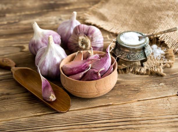 verse knoflookteentjes en lamp met zout shaker op rustieke tafel - zout smaakstof stockfoto's en -beelden