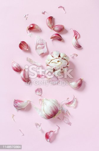 Fresh garlic on a light pink background top view