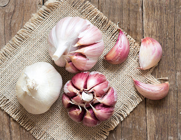 fresh garlic on wooden background - garlic stock photos and pictures