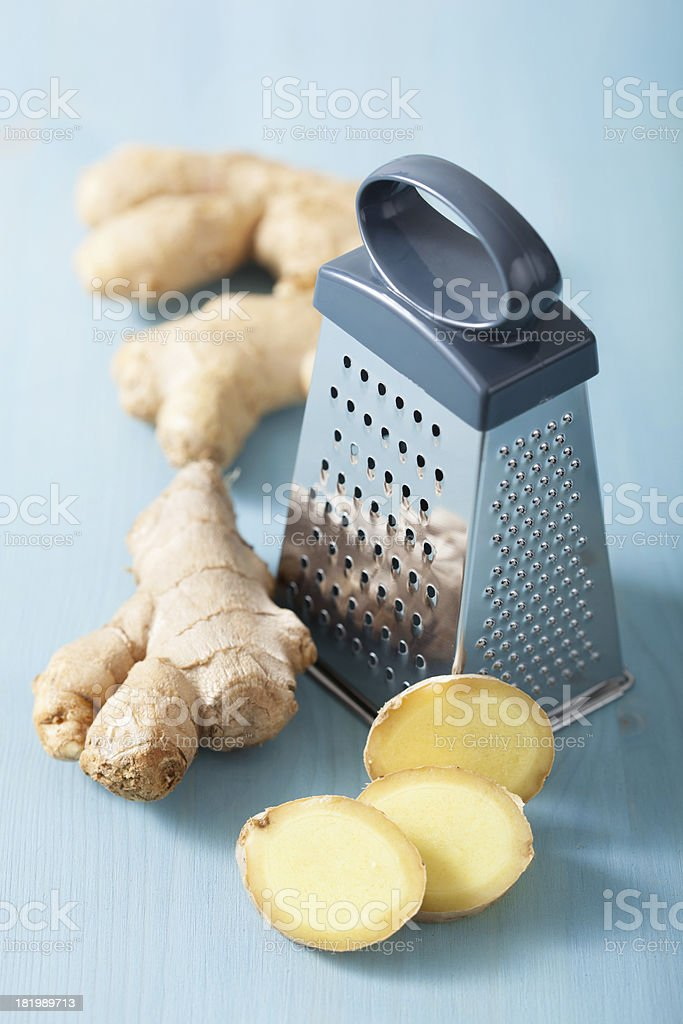 fresh ginger and grater over blue royalty-free stock photo