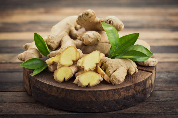 fresh ginger root on the wooden table - ginger stock photos and pictures