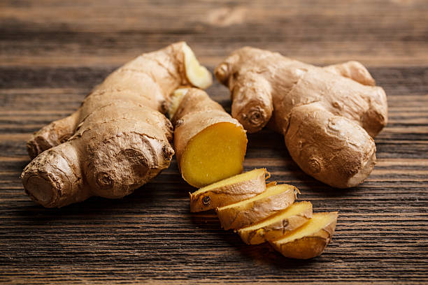 fresh ginger whole and chopped on rustic wood surface - ginger stock photos and pictures