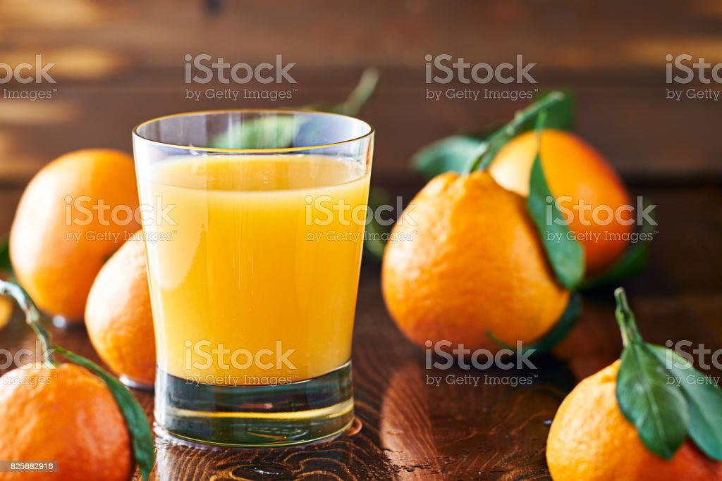 fresh glass of orange juice on rustic table top