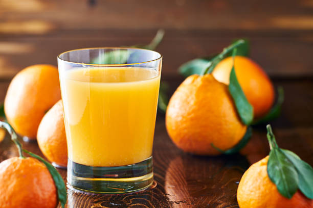 fresh glass of orange juice on rustic table top stock photo
