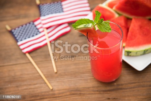 This is an outdoor photograph of a plate of sliced triangle watermelon sitting on a plate of a plate of sliced triangle watermelon sitting on a plate with a glass of watermelon juice and mint