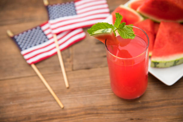 Fresh glass of watermelon juice and mint leaf with slices of watermelon in the background stock photo