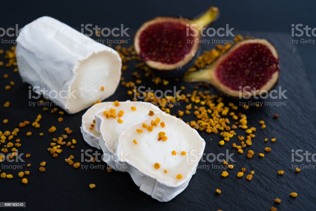 Fresh goat cheese with pollen and figs on black background, stock photo