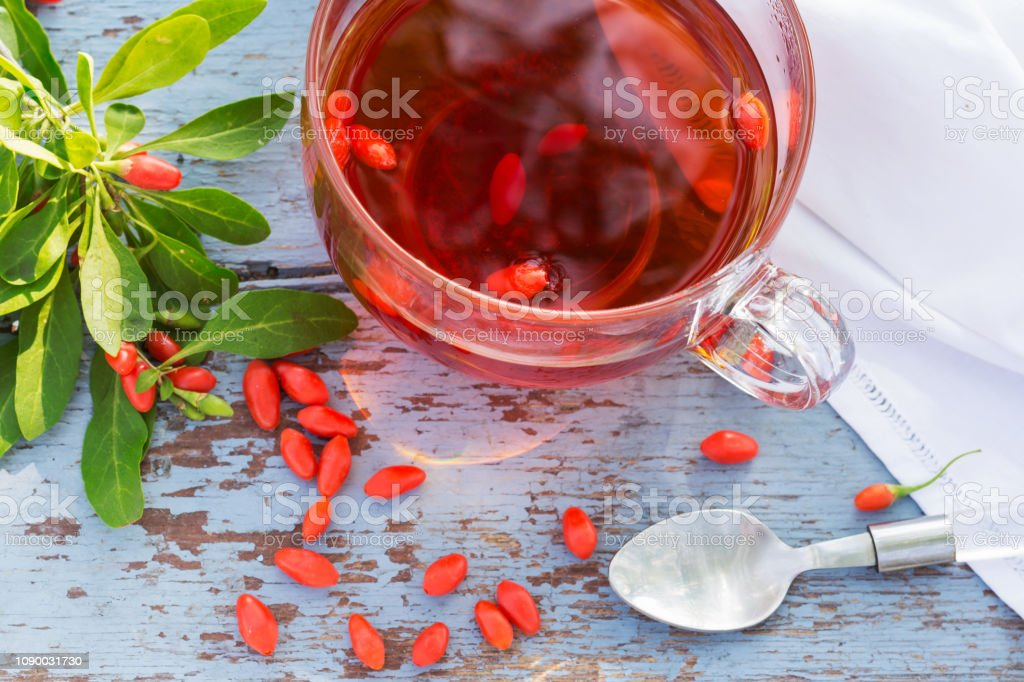 Fresh Goji Berries Tea In A Glass Cup On A Wooden Table Stock