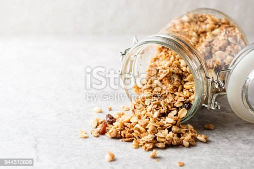 Fresh granola in glass jar on gray stone background. Selective focus. Copy space.