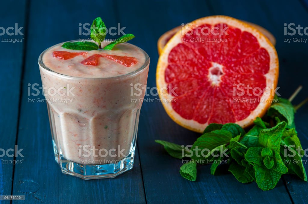 Fresh grapefruit smoothie with mint on wooden table royalty-free stock photo