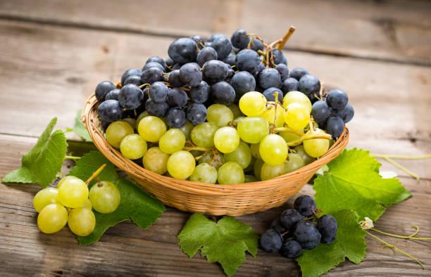 uva fresca en la cesta - grapes fotografías e imágenes de stock