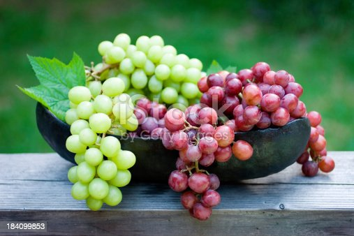Beautiful sweet globes of goodness.  A freshly picked harvest of green and red grapes at a vineyard in a black hand wrought iron bowl.  Shallow dof.
