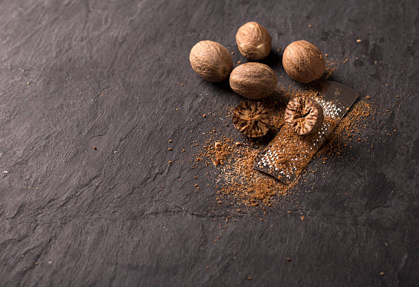 fresh grated nutmeg fresh grated nutmegs and whole ones over black background nutmeg stock pictures, royalty-free photos & images