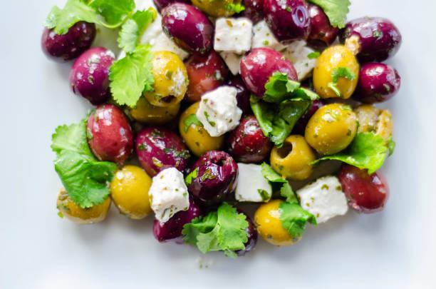 Salada grega fresca baseada em azeitonas verdes e pretas com partes de queijo e de salsa brancos do feta - foto de acervo