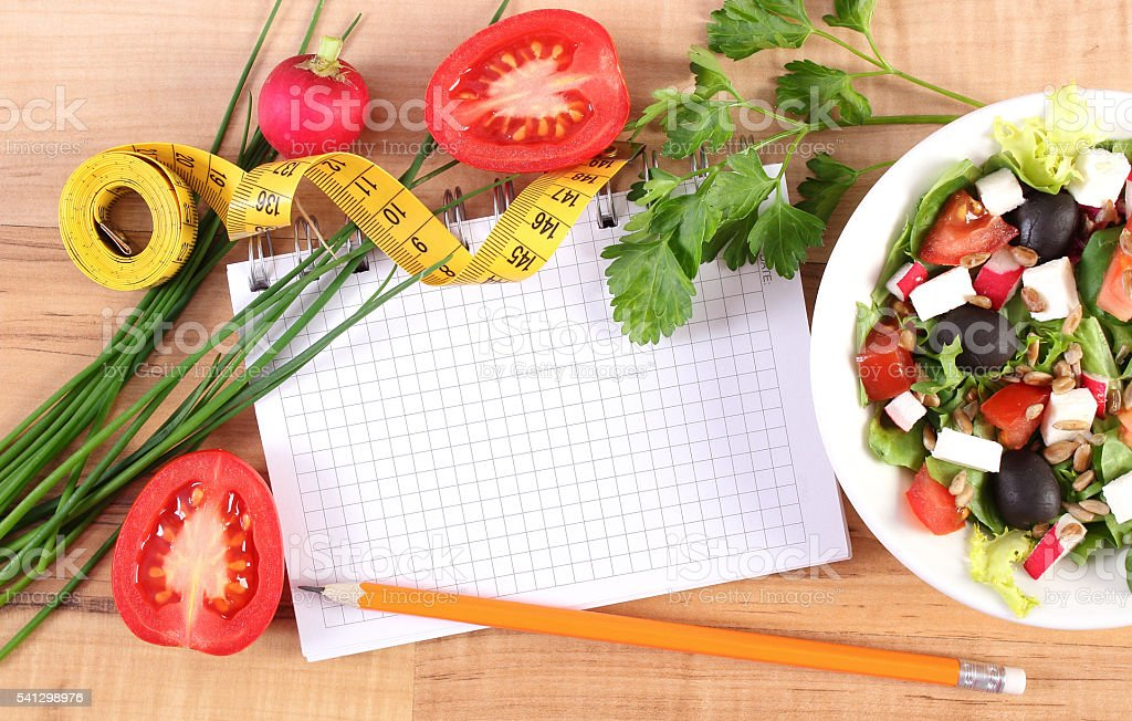 Fresh greek salad with vegetables, centimeter and notepad for notes stock photo