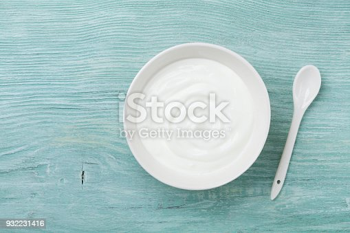 istock Fresh greek yogurt in bowl on rustic wooden table top view. 932231416