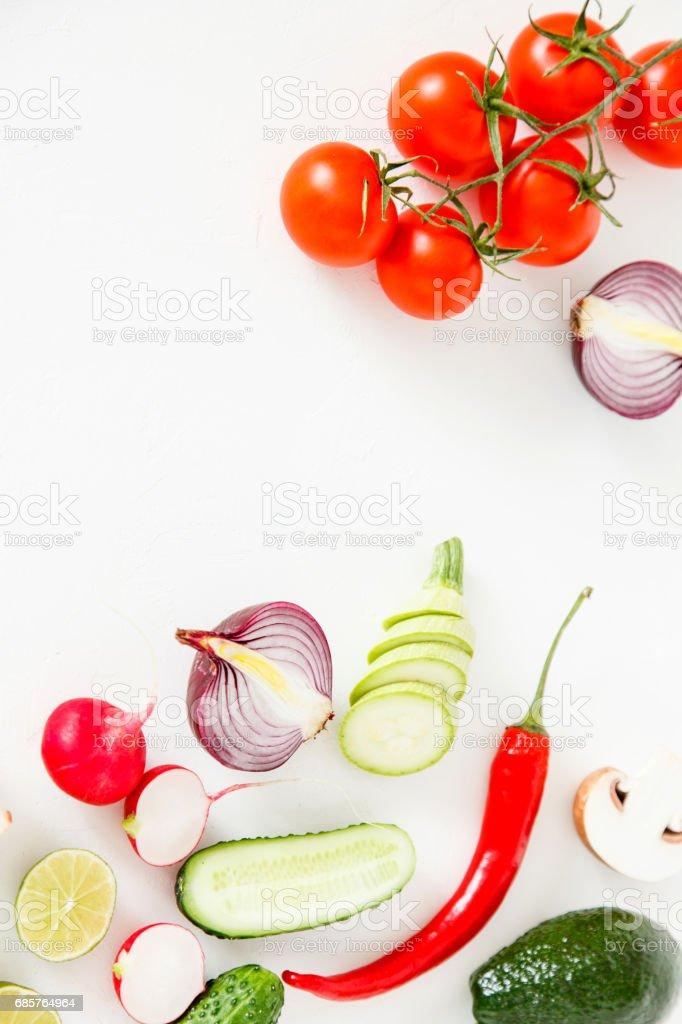 Färska gröna och röda grönsaker ligga på en vit bakgrund, vegetarianmat. royaltyfri bildbanksbilder