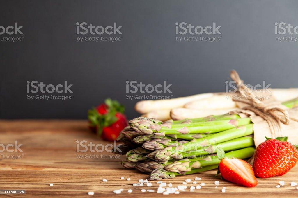 Frischer grüner Spargel mit Erdbeeren auf rustikalem Holztisch – Foto