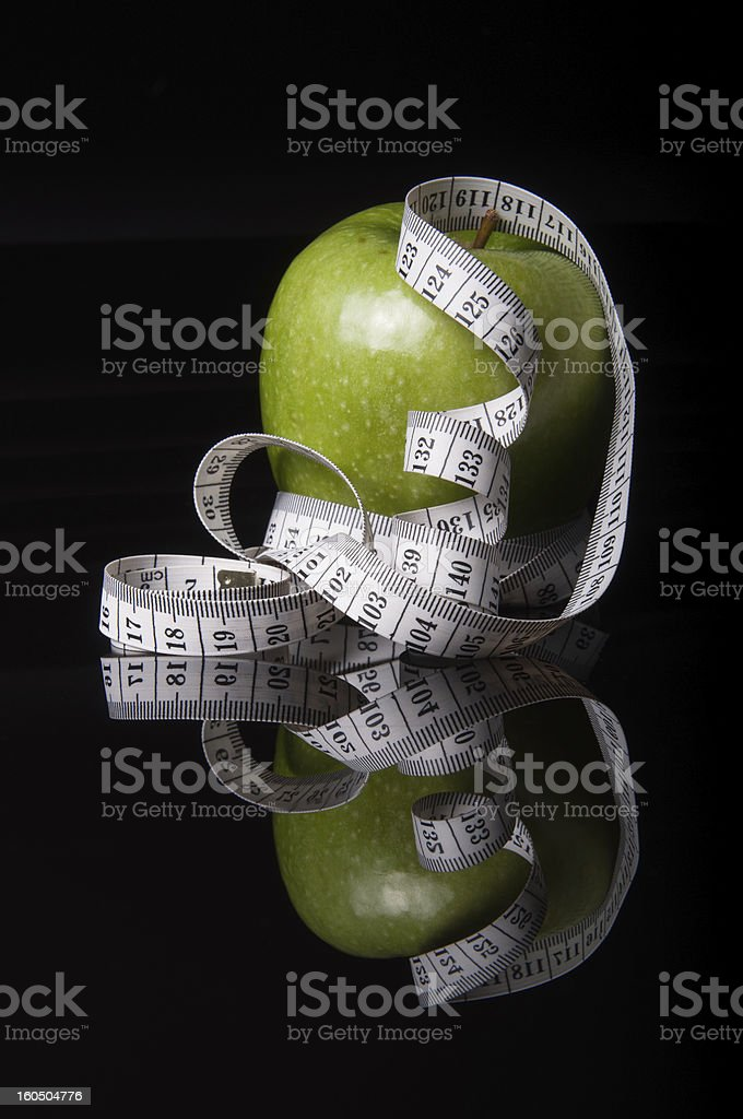 fresh green apple surrounded by white tapeline royalty-free stock photo