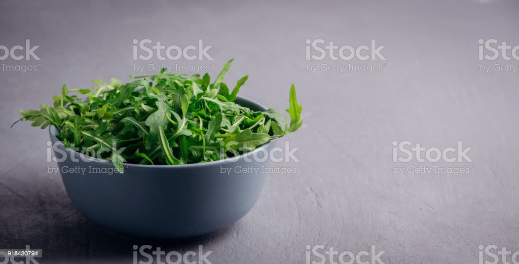 Fresh green arugula in bowl on grey stone background. Arugula is rich in vitamins and trace elements. Selective focus. Top view image. Copyspace for your text. Fashion magazine filter. stock photo