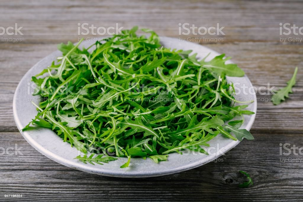Fresh green arugula salad leaves in a bowl on a wooden background. stock photo
