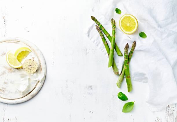 Frischer grüner Spargel und Zitrone auf weißem Holzrücken. Symbolbild. Wohnung gelegt. Kopierplatz – Foto