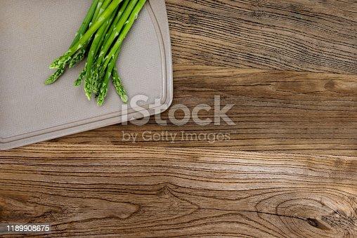 Fresh green asparagus on cutting board.