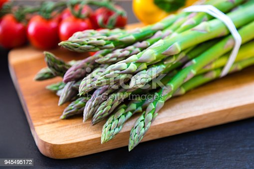 Bunch of fresh green asparagus on a wooden cutting board in the kitchen. Asparagus is a healthy vegetable high in vitamin K and antioxidants.