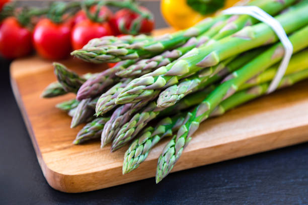 fresh green asparagus on wooden cutting board - asparagus stock pictures, royalty-free photos & images